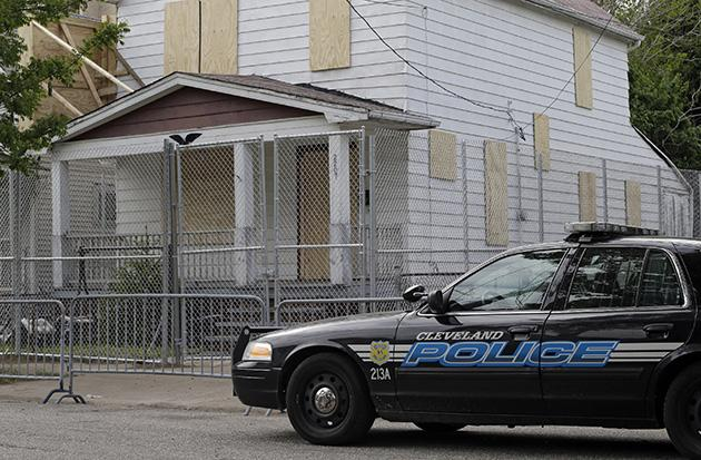 A patrol car in front of Ariel Castro's boarded-up home in Cleveland. (Mark Duncan/AP)
