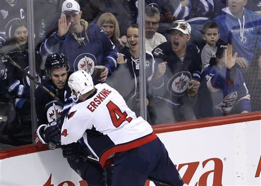 Washington Capitals' John Erskine (4) checks Winnipeg Jets' Andrew Ladd (16) during firs-period NHL hockey game action in Winnipeg, Manitoba, Saturday, March 2, 2013. (AP Photo/The Canadian Press, John Woods)