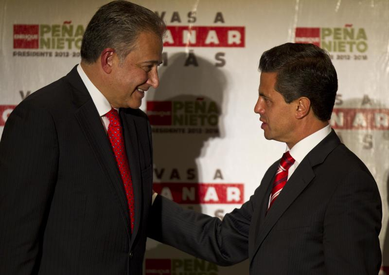 FILE -  In this June 14, 2012 file photo, then presidential candidate Enrique Pena Nieto, right, of the Institutional Revolutionary Party, greets retired Colombian Gen. Oscar Naranjo during a press conference in Mexico City. Naranjo, who was named top security advisor by President-elect Pena Nieto, said Friday, July 6, 2012, that he is recommending the creation of elite units of police and troops who will target not just major drug traffickers but also lower-level cartel hitmen as a way of swiftly reducing violence. (AP Photo/Christian Palma, File)