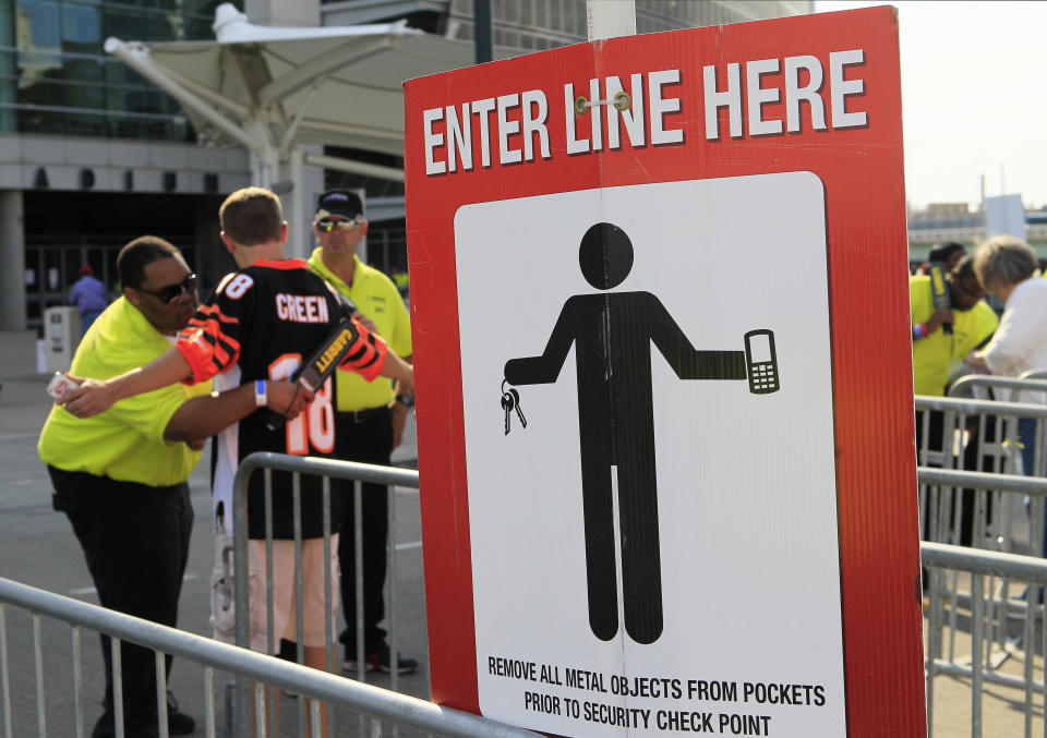 FILE - In this Aug. 17, 2013, file photo, a security guard wands a Cincinnati Bengals fan outside Paul Brown Stadium prior to an NFL preseason football game between the Bengals and Tennessee Titans, in Cincinnati. (AP Photo/Tom Uhlman, File)