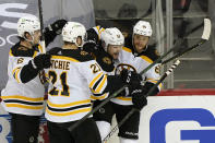 Boston Bruins teammates surround center Sean Kuraly (52) after Kuraly scored a goal during the third period of an NHL hockey game against the New Jersey Devils, Tuesday, May 4, 2021, in Newark, N.J. From the left are Bruins defenseman Mike Reilly (6). left-wing Nick Ritchie (21), Kuraly, and right-wing David Pastrnak (88). (AP Photo/Kathy Willens)