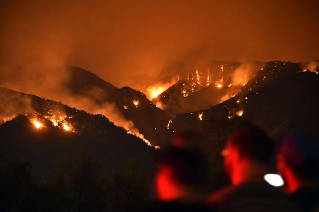 <p>People watch flames from the Holy Fire outside Glen Ivy Hot Springs in Corona, California, southeast of Los Angeles on Aug. 10, 2018. (Photo: Robyn Beck/AFP/Getty Images) </p>