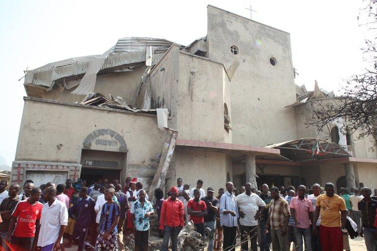 People stand in front of St Theresa Catholic Church after a bombing in Nigeria's capital Abuja on December 25, 2011