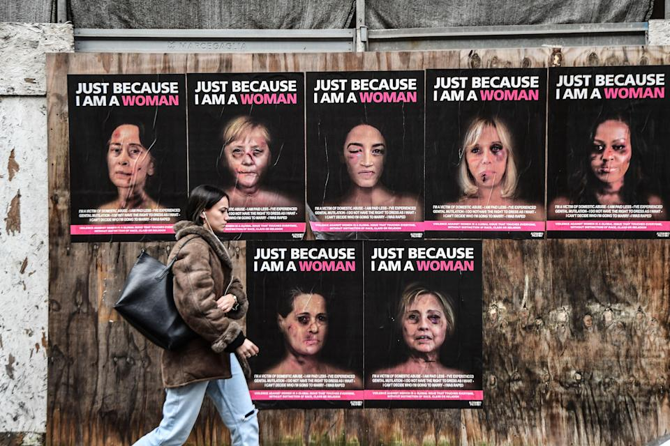 <p>Woman strolls past series by Italian artist aleXsandro Palombo showing high-profile politicians as victims of gender-based violence </p> (AFP via Getty Images)