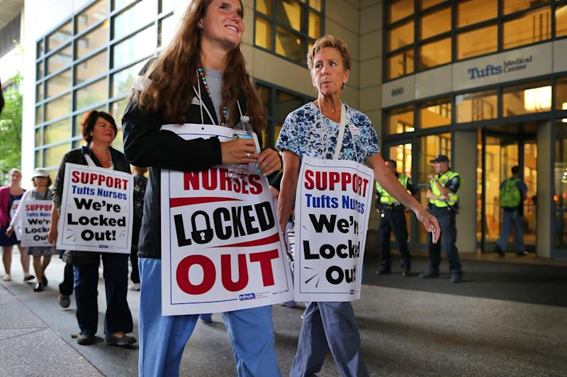 Tufts Medical Center nurses picket in Boston on July 13 after being locked out after a 24-hour strike. One of the sources of stress nurses report is not being included in the decision-making process at health facilities. (John Tlumacki/The Boston Globe via Getty Images)