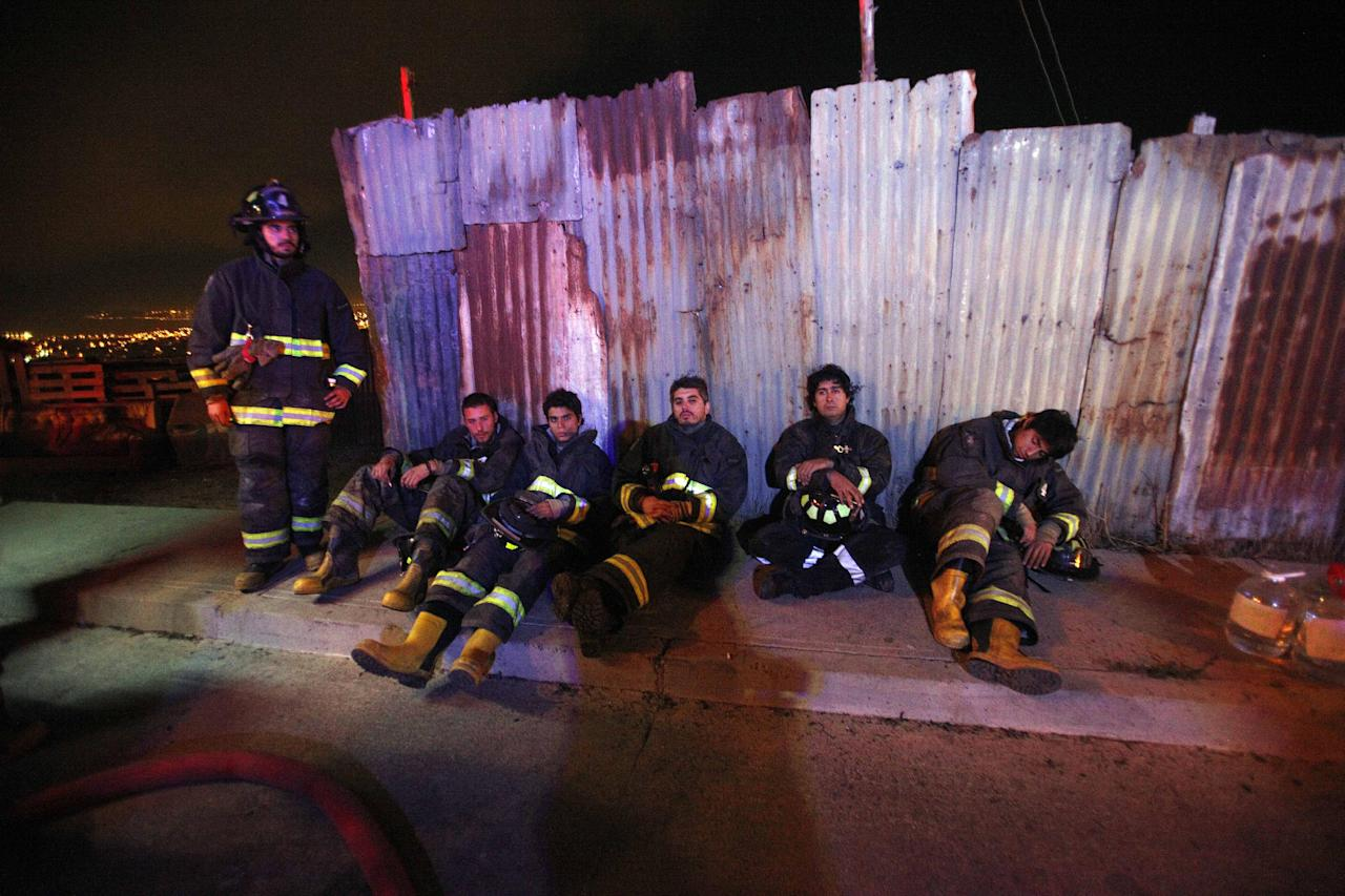 Firefighters take a break from battling blazes after an out of control forest fire reached urban areas in the city of Valparaiso, Chile, early Monday April 14, 2014. Firefighters struggled for a second night to contain blazes that reached this port city, killing at least a dozen people, destroyed hundreds homes and has forced the evacuation of thousands. (AP Photo/Luis Hidalgo)