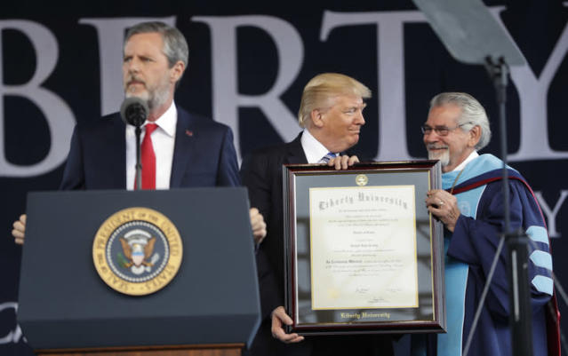 Trump receives an honorary degree from Liberty University provost Ronald E. Hawkins, right, before giving the commencement address. Speaking at the podium is university president Jerry Falwell Jr. (AP Photo/Pablo Martinez Monsivais)