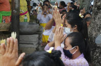 Women wearing face masks as a precaution against the new coronavirus outbreak pray during a Hindu ritual prayer at a temple in Bali, Indonesia, Wednesday, Sept. 16, 2020. (AP Photo/Firdia Lisnawati)