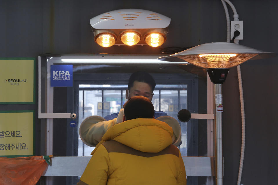 A medical worker in a booth takes a sample from a man at a coronavirus testing site in Seoul, South Korea, Thursday, Jan. 7, 2021. (AP Photo/Ahn Young-joon)