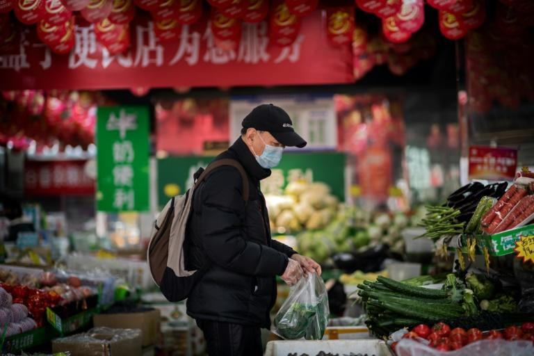 """A man wearing a protective face mask and gloves buys vegetables at a shop in Beijing -- China's President Xi Jinping, in a rare admission, said the country must learn from """"obvious shortcomings exposed"""" by the new coronavirus"""
