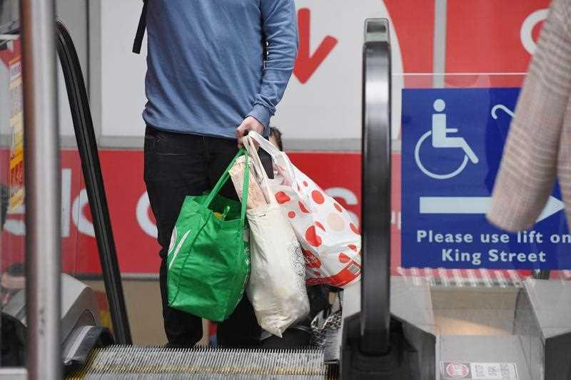 A man carries reusable Coles bags up an escalator in Sydney.