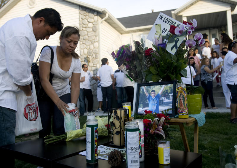 Alex Flores, left, and Silvia Castro place candles at a vigil for Ricardo Portillo, who passed away after injuries he sustained after an assault by a soccer player at a soccer game he was refereeing on April 27, in Salt Lake City on Sunday, May 5, 2013. (AP Photo/The Salt Lake Tribune, Kim Raff)