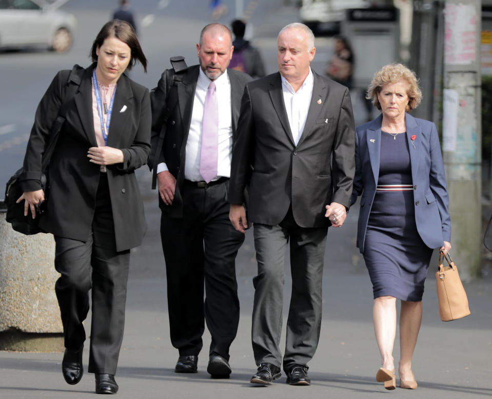 Parents of murdered British backpacker Grace Millane, her father David, second from right, and mother Gillian, right, arrive at the Auckland High Court, in Auckland, New Zealand, Wednesday, Nov. 6, 2019 for the murder trial of a man accused of killing their daughter Grace. Prosecutors say Grace Millane met her killer on the dating app Tinder, and they appeared to be enjoying themselves as they visited several bars before going back to his downtown Auckland apartment. The 27-year-old man accused of killing Millane has pleaded not guilty. His name is being kept secret for now by court order. (Michael Craig/NZ Herald via AP)