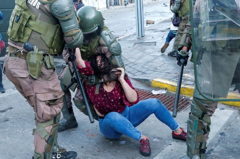 FILE PHOTO: A demonstrator is detained by riot police during a protest against Chile's government in Valparaiso