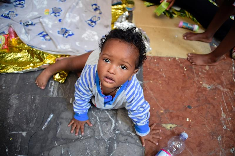 10-month-old Dan from Eritrea waits with his relatives at Milan train station on June 11, 2015, as about 300 migrants, mainly from Eritrea, arrived in the city after fleeing their homeland (AFP Photo/Olivier Morin)
