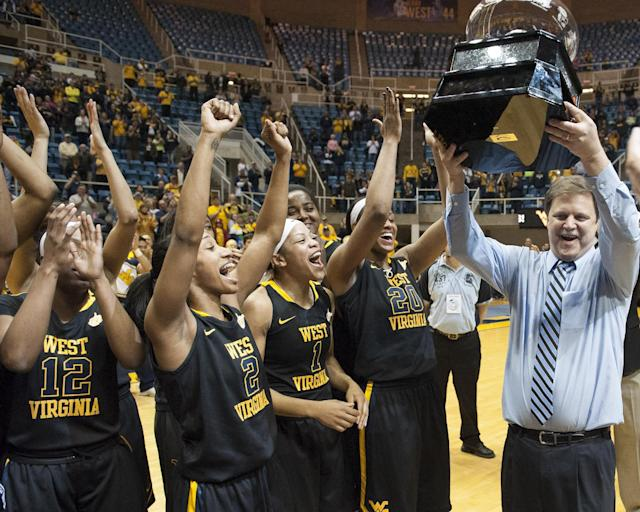 West Virginia's Mike Carey, right, celebrates a share of the Big 12 Conference championship after defeating Kansas during an NCAA college basketball game Tuesday, March 4, 2014, in Morgantown, W.Va. West Virginia won 67-60. (AP Photo/Andrew Ferguson)