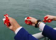 Colleagues of the crew members of Sriwijaya Air flight SJ 182, which crashed into the sea, throw flowers and petals from the deck of Indonesia's Naval ship KRI Semarang as they visit the site of the crash to pay their tribute, at the sea off the Jakarta