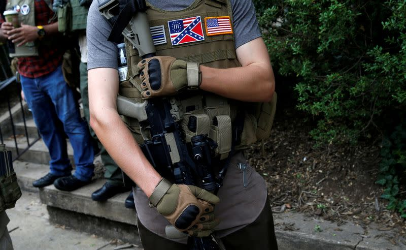 FILE PHOTO: A member of a militia stands near a rally in Charlottesville Virginia