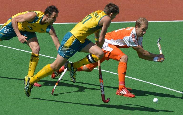 Captain Eddie Ockenden of Australia (centre) challenges Billy Baaker of the Netherlands in the gold medal match at the men's Hockey Champions Trophy tournament in Melbourne. Australia went some way to erasing the pain of their London Olympics flop by winning a record fifth consecutive Champions Trophy in a 2-1 extra-time victory over the Netherlands