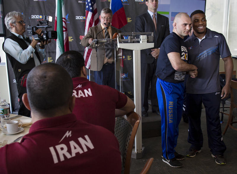 """Saba Khubezhyty, second from right, of Russia shakes hands with USA's Jordan Burroughs of Lincoln, Neb., right, after their 74 kilogram class weigh-in during a news conference at U.N. headquarters, Tuesday, May 14, 2013, announcing the """"Rumble on the Rails"""" wrestling exhibition between the teams from Iran, Russia and the United States. The exhibition, to be held at New York's Grand Central Terminal on Wednesday, is designed to highlight the sport's international appeal and popularity. (AP Photo/Craig Ruttle)"""