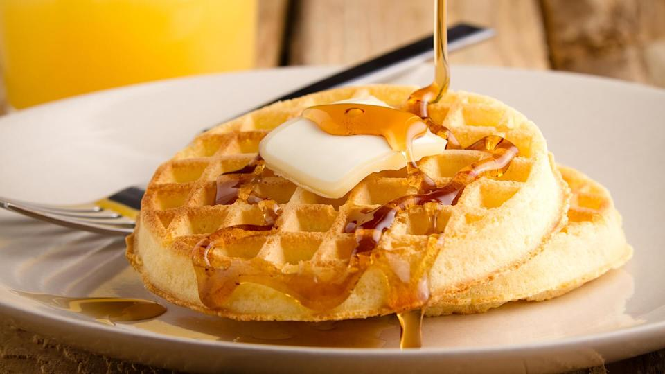 This s a photo of a couple waffles being soaked in syrup.