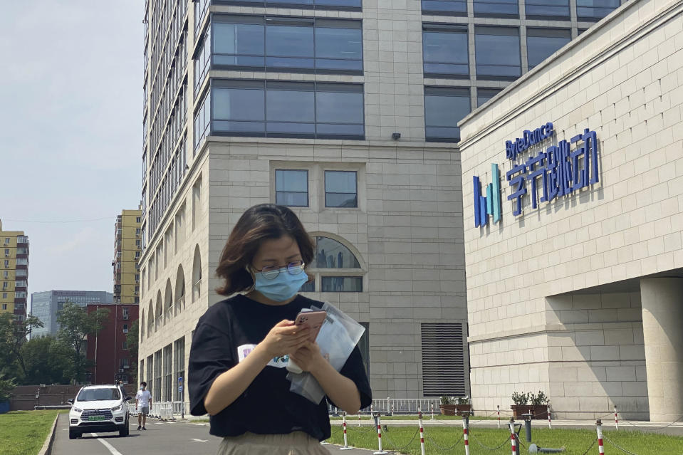 A woman uses her phone as she passes by the ByteDance headquarters in Beijing, China, on Friday, Aug. 7, 2020. President Donald Trump on Thursday ordered a sweeping but unspecified ban on dealings with the Chinese owners of consumer apps TikTok and WeChat, although it remains unclear if he has the legal authority to actually ban the apps from the U.S. TikTok is owned by Chinese company ByteDance. (AP Photo/Ng Han Guan)