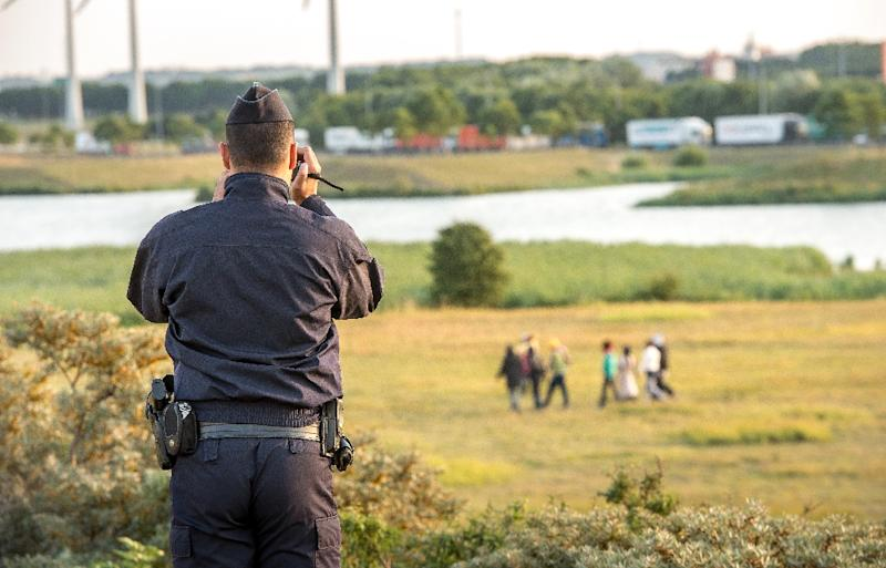 A French gendarme films migrants trying to enter the Eurotunnel in Coquelles near Calais, northern France, on July 31, 2015 (AFP Photo/Philippe Huguen)