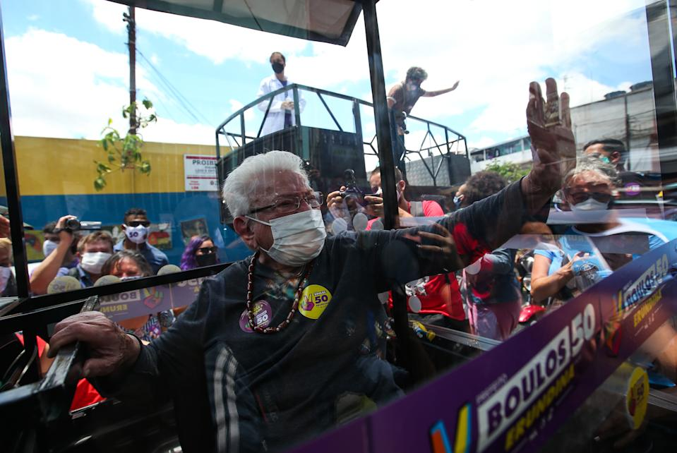 "SAO PAULO, BRAZIL - NOVEMBER 21: Luiza Erundina, 85, Guilherme Boulos's candidate for vice-mayor for the city of Sao Paulo for the Socialism and Freedom Party (PSOL) greets  and talks to supporters from inside the ""Cata-voto"" (Vote Catcher), a car surrounded with a plastic booth like the 'Popemobile' to protect herself from the coronavirus during a walking rally on November 21, 2020 in Sao Paulo, Brazil. Municipal elections in the city of Sao Paulo advance to a second round in which Guilherme Boulos faces Bruno Covas, current mayor of the city for the Brazilian Social Democracy Party (PSDB). (Photo by Alexandre Schneider/Getty Images)"