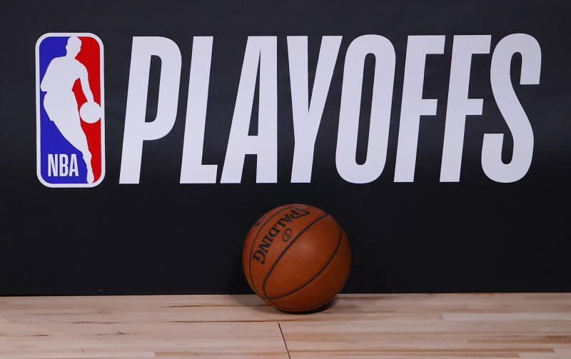 A basketball sits next to an NBA Playoffs logo.