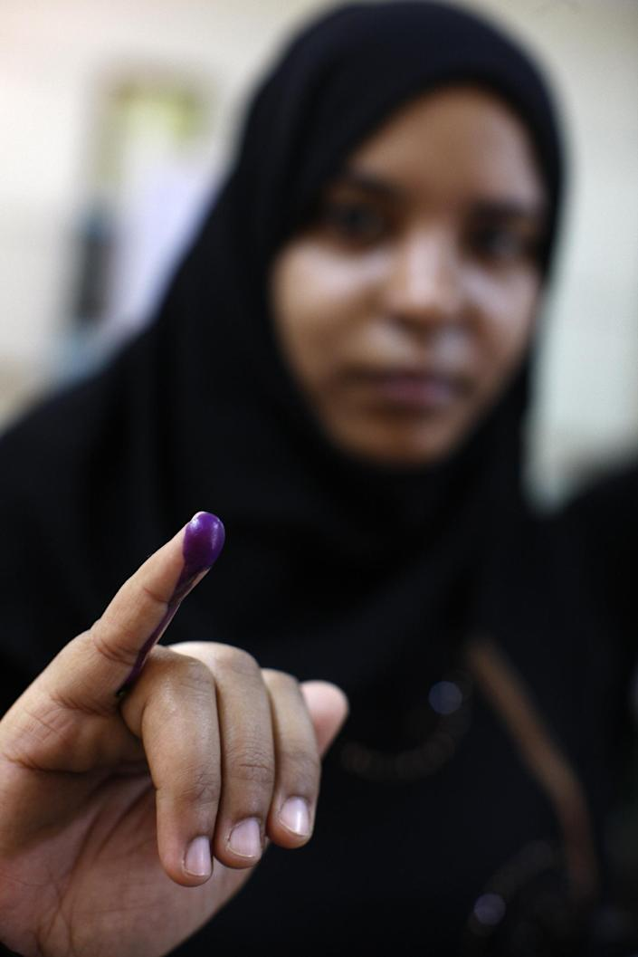An Egyptian woman shows the ink on her finger after voting in the presidential election Thursday, May 24, 2012, in the Mataraya neighborhood of Cairo, Egypt. n a wide-open race that will define the nation's future political course, Egyptians voted Thursday on the second day of a landmark presidential election that will produce a successor to longtime authoritarian ruler Hosni Mubarak. (AP Photo/Frederik Persson)