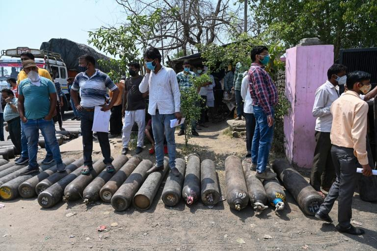 People wait outside to refill their cylinders with oxygen for Covid-19 patients, at a refilling centre in Moradabad