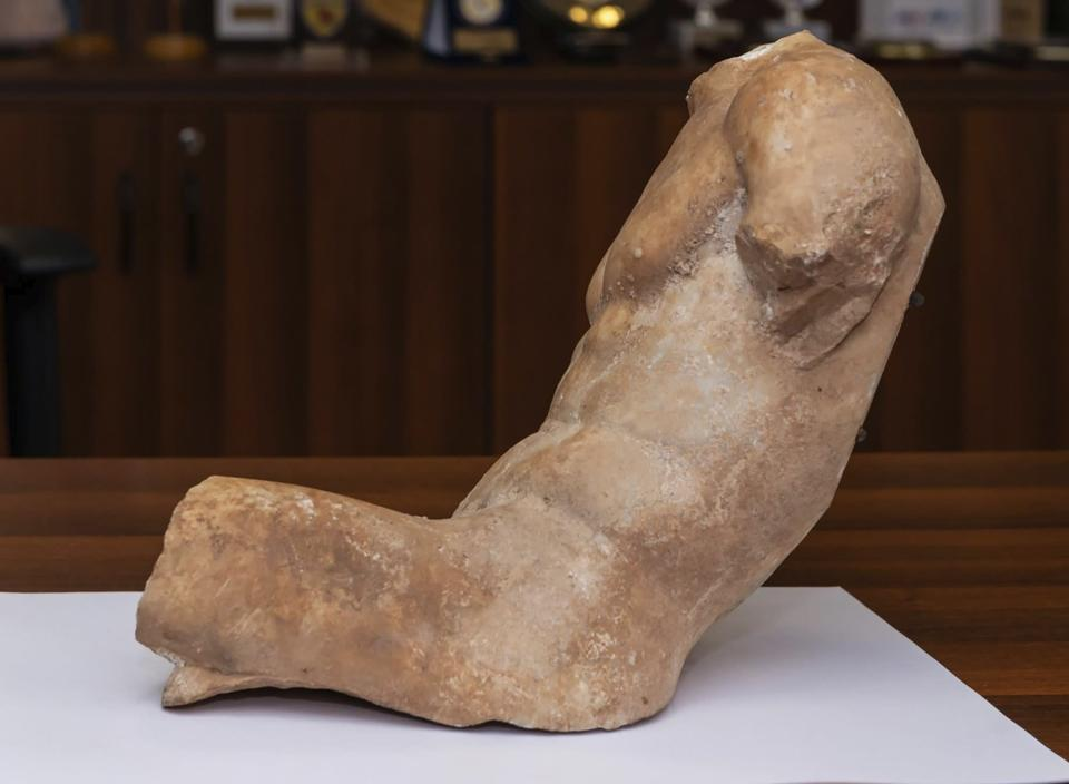 """In this Friday, March 19, 2021, photo provided by the Greek Police shows a 5th century B.C. statue about 37 centimeters (14.5 inches), depicting a seated young man who slightly reclines. Greek police say a man has been arrested on suspicion of antiquities smuggling for trying to sell an ancient marble statue of """"exceptional artwork and significant archaeological value"""" that once likely adorned the pediment of a building on Athens' famed Acropolis or the slopes around it. (Greek Police via AP)"""