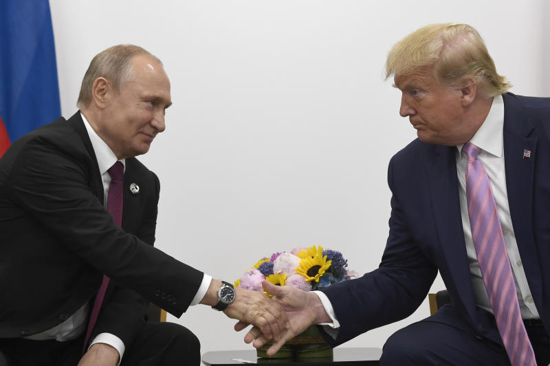 FILE - In this June 28, 2019, file photo President Donald Trump, right, shakes hands with Russian President Vladimir Putin, left, during a bilateral meeting on the sidelines of the G-20 summit in Osaka, Japan. For the past three years, the administration has careered between President Donald Trump's attempts to curry favor and friendship with Vladimir Putin and longstanding deep-seated concerns about Putin's intentions. (AP Photo/Susan Walsh, File)