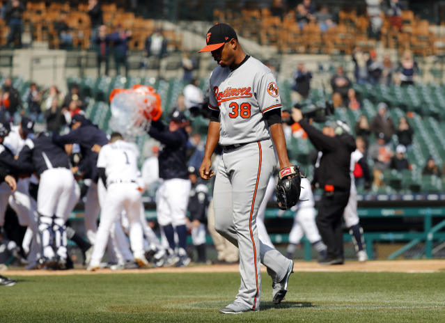 Baltimore Orioles relief pitcher Pedro Araujo (38) walks off the field as the Detroit Tigers, background, celebrate Dixon Machado's walk-off solo home run in the ninth inning of a baseball game in Detroit, Wednesday, April 18, 2018. Detroit won 6-5. (AP Photo/Paul Sancya)
