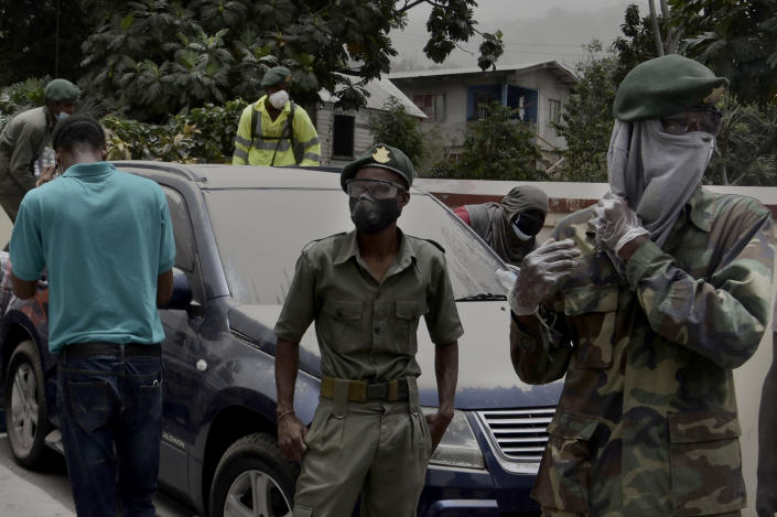 Soldiers and residents stand next to a car covered in volcanic ash in Kingstown, on the eastern Caribbean island of St. Vincent, Saturday, April 10, 2021, due to the eruption of the La Soufriere volcano. (AP Photo/Orvil Samuel)