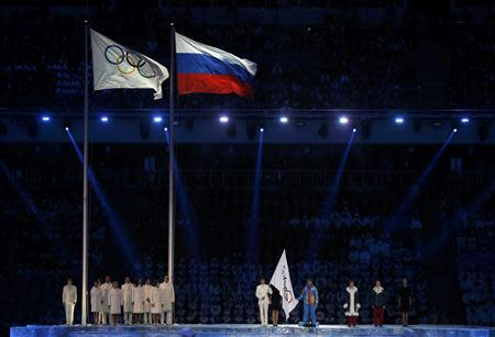 Participants stand after the Olympic flag (L) was raised during the opening ceremony of the 2014 Sochi Winter Olympics, February 7, 2014. REUTERS/Phil Noble
