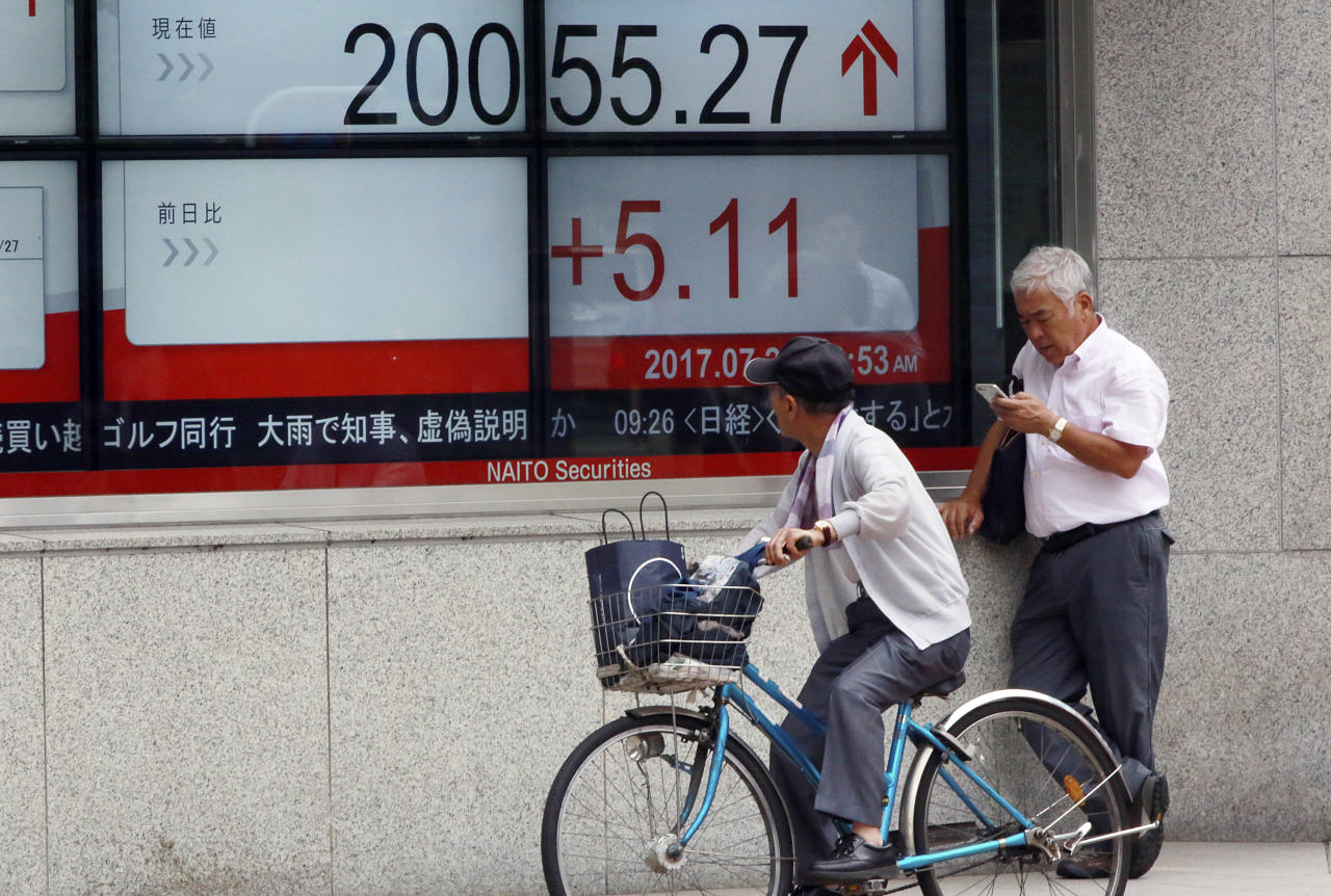 <p> A man on bicycle looks at an electronic stock board showing Japan's Nikkei 225 index at a securities firm in Tokyo Thursday, July 27, 2017. Asian shares were mostly higher Thursday, supported by strong corporate earnings and the Federal Reserve's decision to pause its slow-moving campaign to raise interest rates. (AP Photo/Eugene Hoshiko) </p>