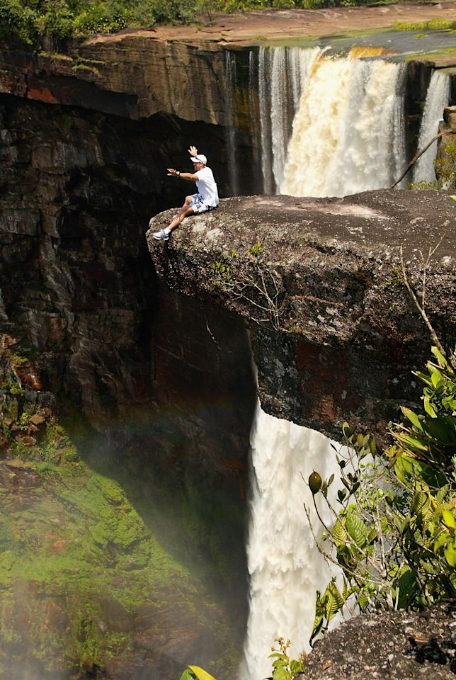 GEORGETOWN - APRIL 9:  Matthew Hayden of Australia takes in the sights at Kaieteur Falls on a rock ledge over a 741 foot drop during a team trip to Kaieteur and Orinduik Falls in Guyana on April 9, 2003. (Photo by Hamish Blair/Getty Images)
