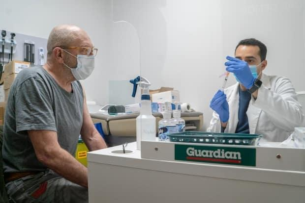 Wayne Milling looks on as his dose of the AstraZeneca COVID-19 vaccine is being prepared on Wednesday, March 17, 2021, at the Guardian Snowdon Pharmacy in Toronto. Starting Monday, Ontarians over the age of 75 can start booking vaccine appointments through the province's online system. (Sam Nar/CBC - image credit)