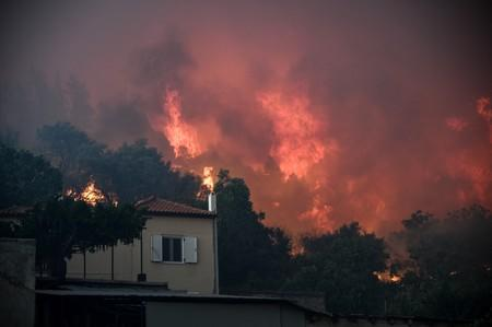 Flames rise next to a house as a wildfire burns at the village of Kontodespoti, on the island of Evia