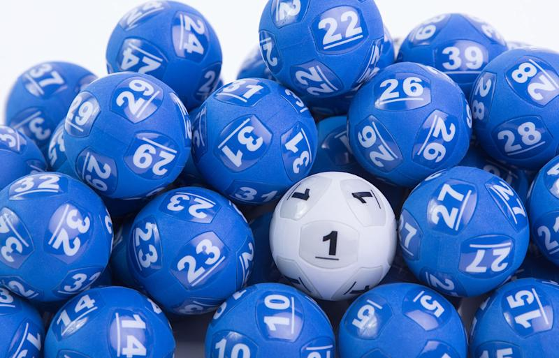 Pictured are blue Powerball lotto balls with one white ball among them.