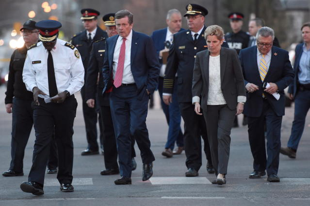 <p>Toronto Police Chief Mark Saunders, front left, Toronto Mayor John Tory, Premier Wynne and Ralph Goodale, Federal Minister of Public Safety and Emergency Preparedness walk together towards a news conference after viewing the scene where a rented van plowed down a crowded Toronto sidewalk on Monday, April 23, 2018. (Photo: Nathan Denette/The Canadian Press via AP) </p>