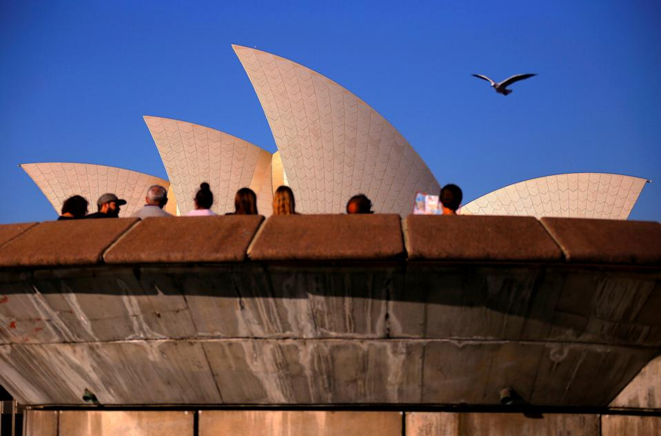 Picture of the iconic Sydney opera house, a popular tourist attraction, with travellers seen outside looking at the building.
