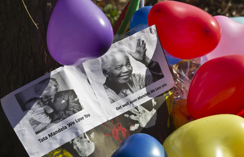 """Balloons, hand-prints and get well messages left by children from the """"Ring-Ting"""" kindergarten lie outside the entrance to the Mediclinic Heart Hospital where former South African President Nelson Mandela is being treated in Pretoria, South Africa Friday, June 14, 2013. Nelson Mandela's health is improving but the 94-year-old beloved anti-apartheid hero remains in serious condition, South Africa's president said Thursday. (AP Photo/Ben Curtis)"""