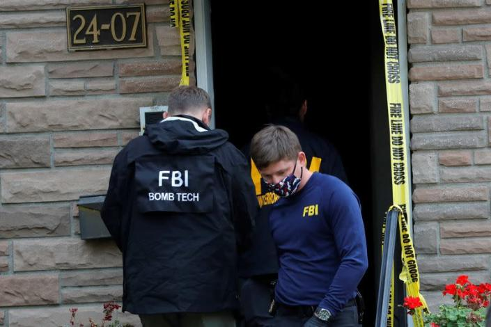 FBI officers outside house where police say bomb-making materials were found, in New York