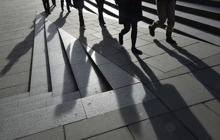 Workers are seen walking during the lunch hour in the City of London, in Britain