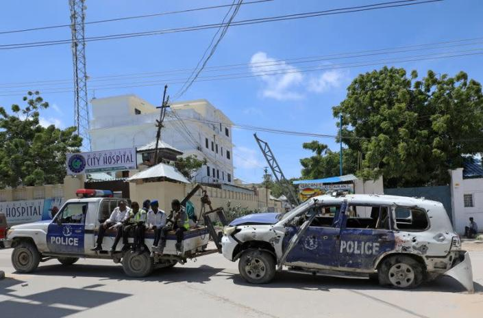 FILE PHOTO: Somali police officers tow their car from the scene of a roadside explosion in Hodan district of Mogadishu