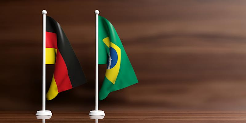 Brazil and Germany miniature flags on wooden background. 3d illustration