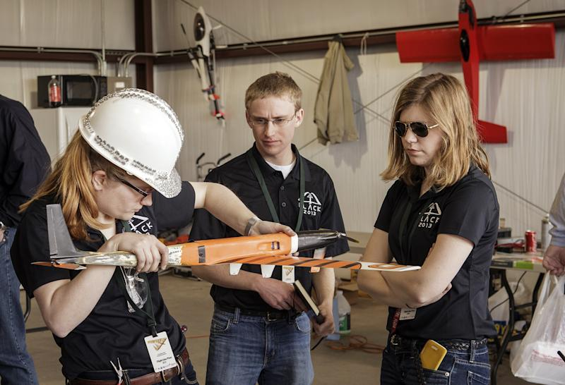 In this April 2013 photo provided by Oklahoma State University, Team Black members from left, Amelia Wilson, Nathan Woody and Alyssa Avery prepare their aircraft for flight during SpeedFest III at Oklahoma State University, in Stillwater, Okla. Researchers at OSU are designing and building sleek, Kevlar-reinforced unmanned aircraft _commonly known as drones_ to fly into the nation's worst storms and send back real-time data to first responders and forecasters about how fierce they might become. (AP Photo/ Oklahoma State University, Gary Lawson)
