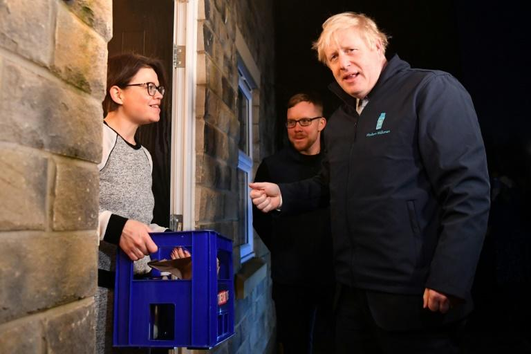 """""""This could not be more critical. It could not be tighter,"""" said Johnson, shown here delivering milk to a voter in Guiseley, northern England (AFP Photo/Ben STANSALL)"""